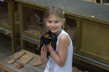 """Giuliana (9 Jahre) mit ihrem Patentier """"Lilly"""": """"Hier lernt man viel über Tiere, das finde ich toll."""" Foto: Jan Engelken"""